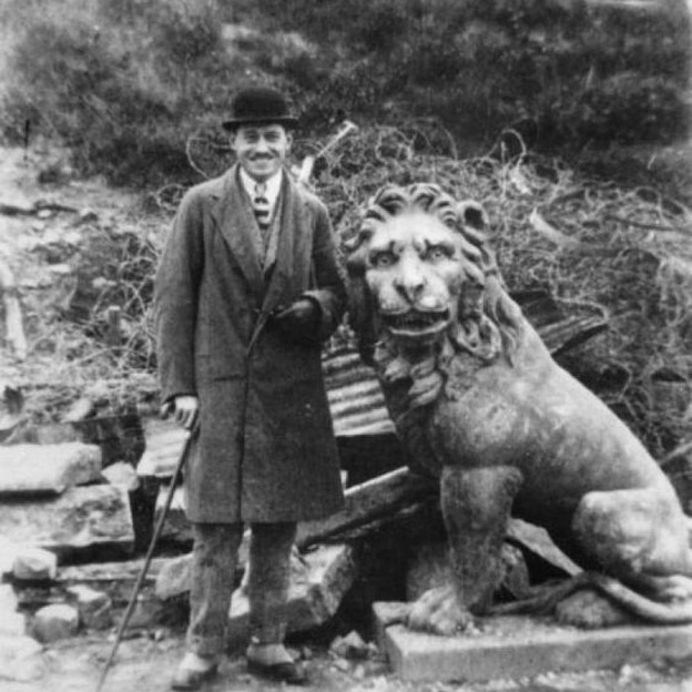 man stands beside carved lion at the menion gate