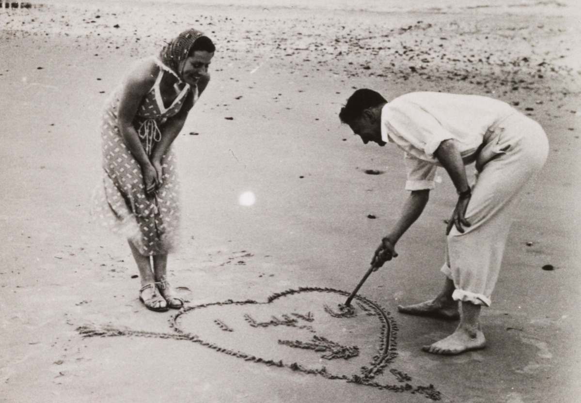 Man writes 'I LOVE U' in the sand for his sweetheart, 1920-60.