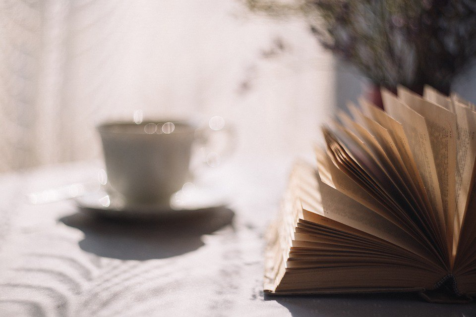 A book and a cup of tea sit on the table