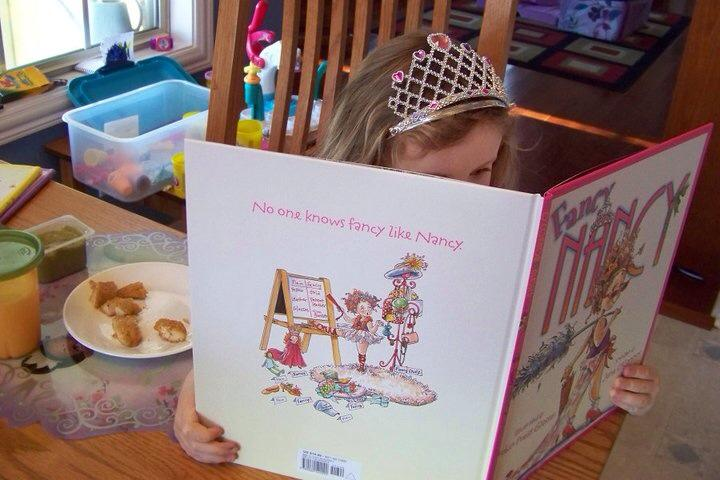 A small girl reads a book