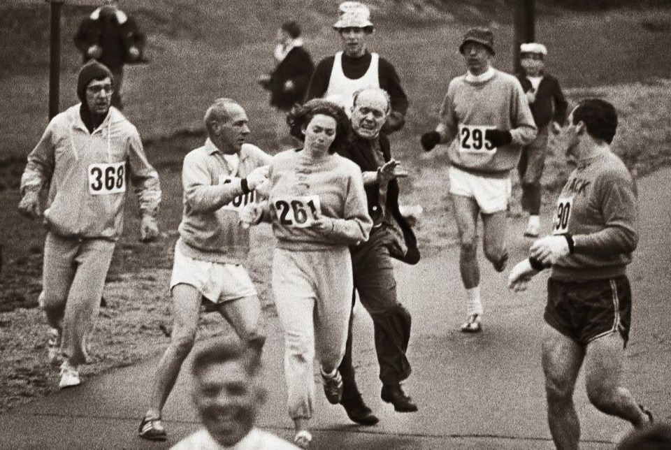 Katherine Swizer running the Boston Marathon while men try to stop her womens rights