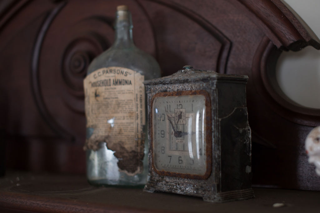 a clock and a bottle on the mantle