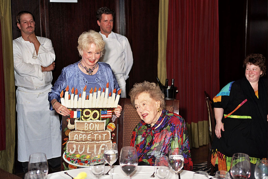 Chef Julia Child is presented with a card designed by gallery owner, Nancy Thomas, during a charity pre-birthday dinner