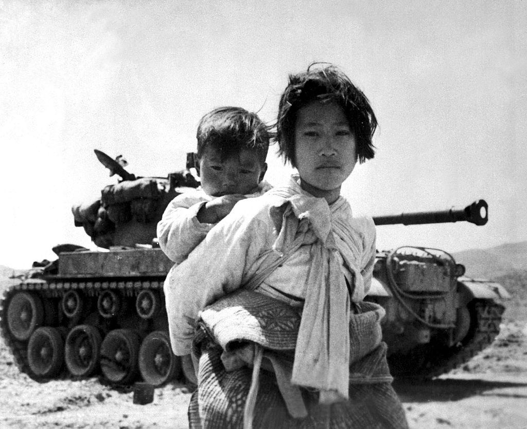 A war weary Korean girl walks by a stalled M-26 tank