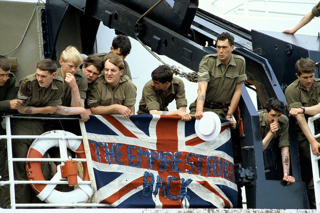 Troops hold a British Union Jack over the ships railings, with the slogan which reads ' The Empire Strikes Back', as they stand on board the deck of the RMS Queen Elizabeth 2