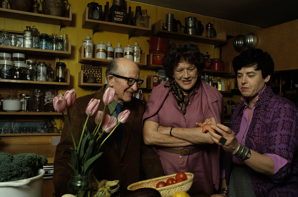 American chef, author, and television personality Julia Child (nee McWilliams, 1912 - 2004) (center) and her husband, Paul Cushing Child (1902 - 1994) look at a small sculptutr held by an unidentified woman in a kitchen, May 1978.