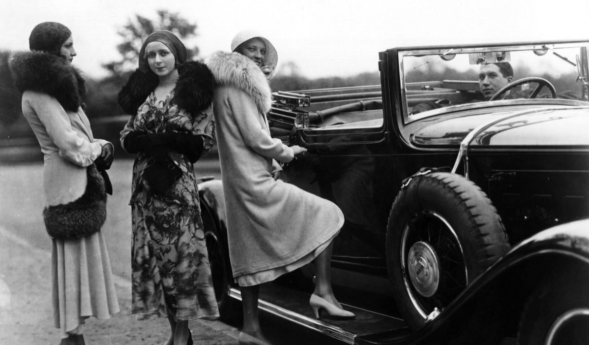 circa 1920: Women standing by a convertible car