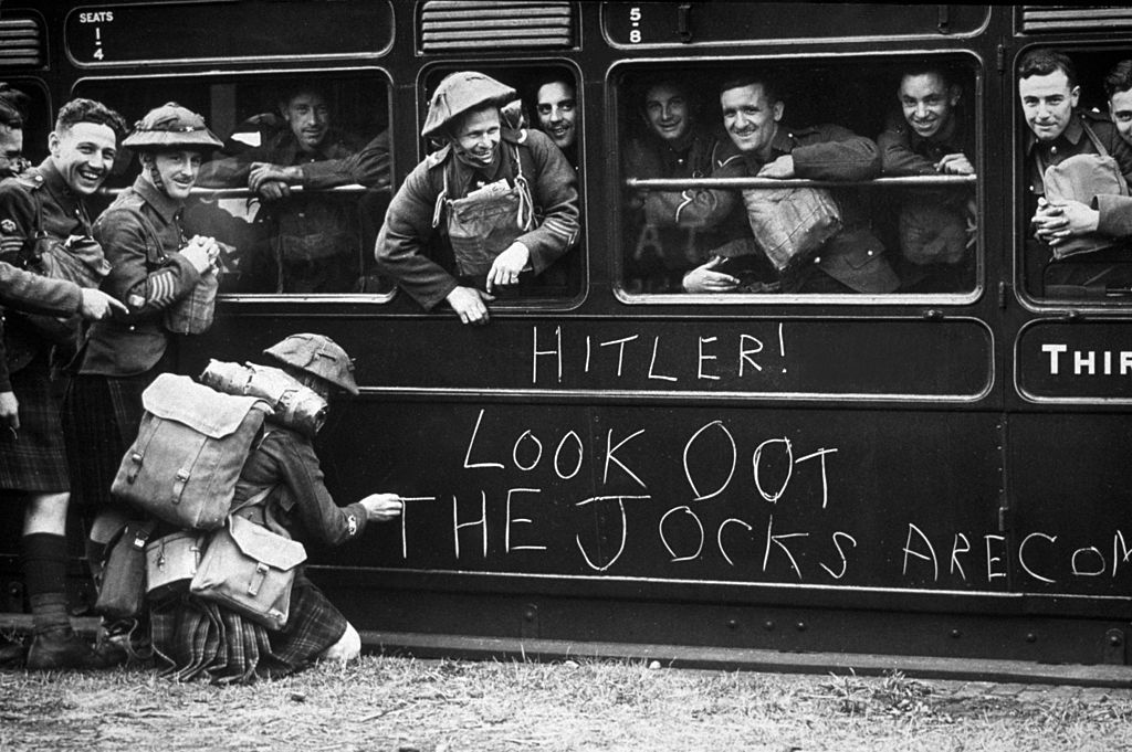 A solider of the Cameron Highlanders chalks a warning to Hitler