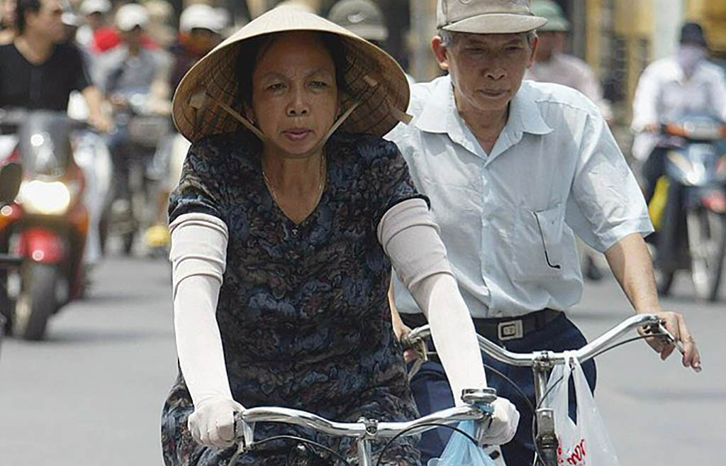Woman rides bike with sleeves to cover her arms from the sun