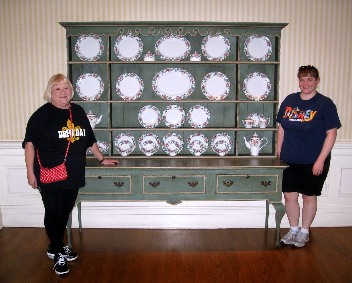 two women stand next to a china cabinet in walt disney world