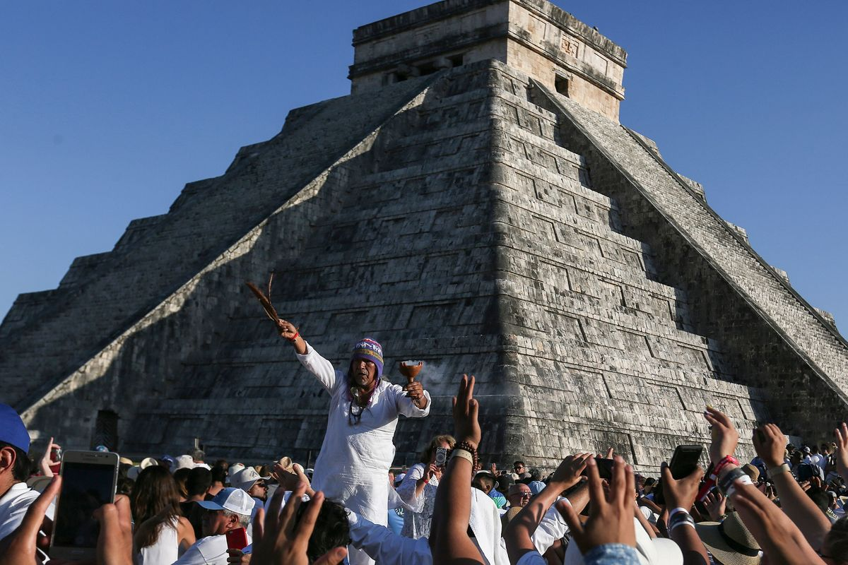 People surround the Kukulcan Pyramid as a shaman performs a spring equinox ritual at the Mayan archaeological site of Chichen Itza