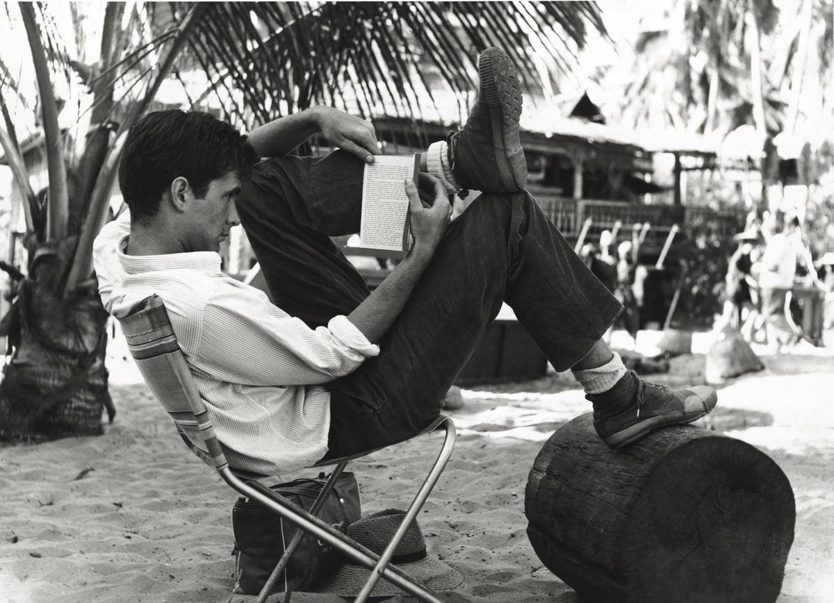 The American actor Anthony Perkins having a rest reading on the set of 'This Angry Age'.