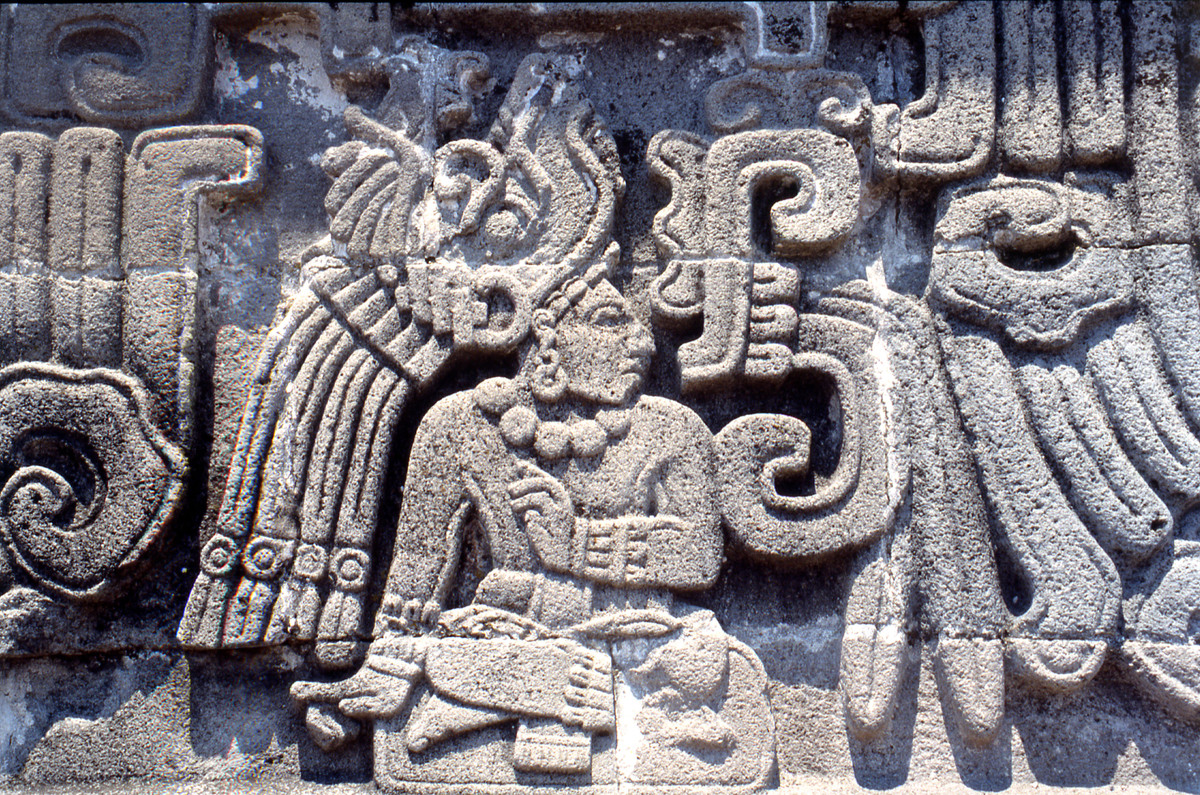 Detail from the Temple of the Feathered Serpent at Xochicalco, showing a richly attired personage, so called 9 Wind (the birthdate of the god Quetzalcoatl Feathered Serpent), The style owes much to lowland Classic Maya representations of seated rulers