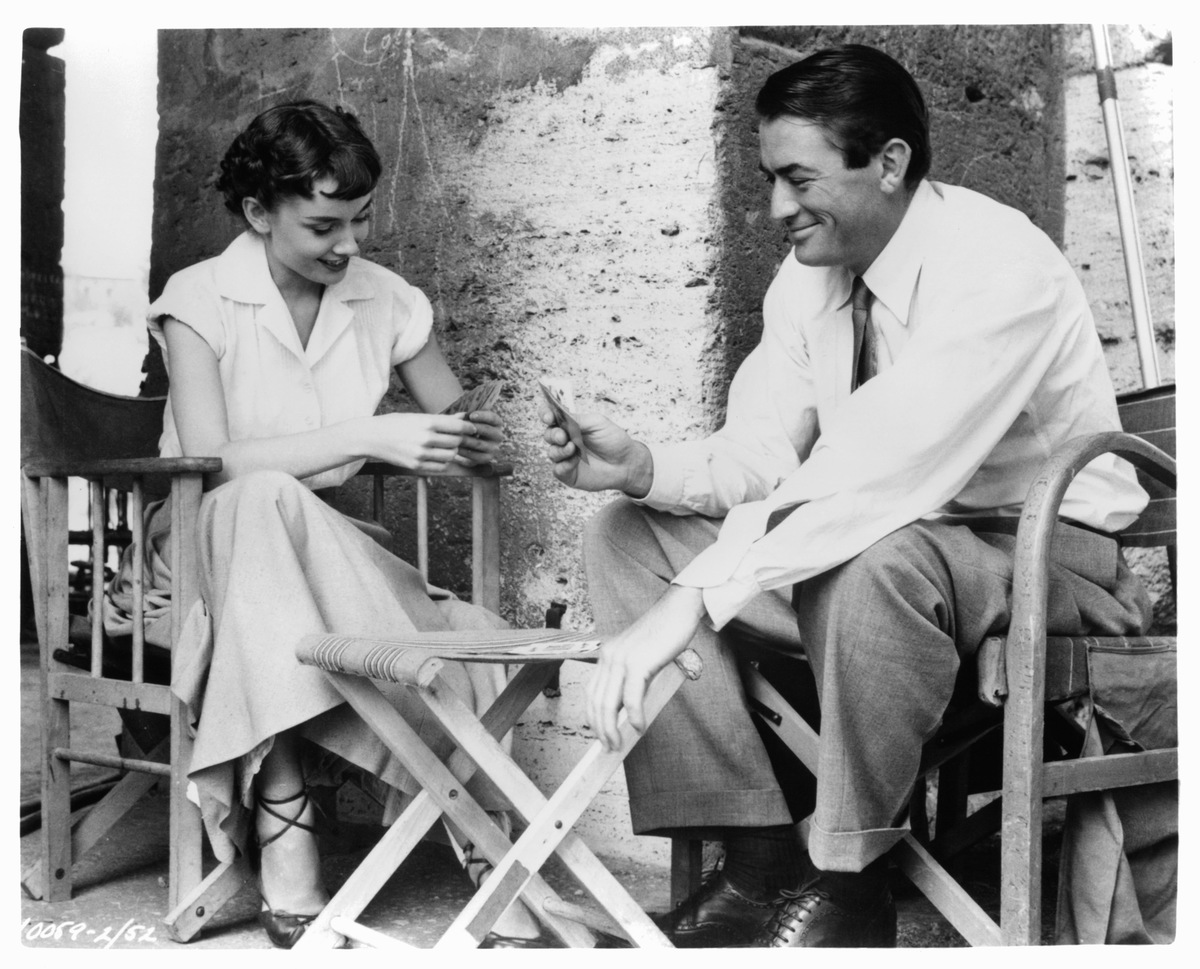 Audrey Hepburn plays cards with Gregory Peck in a scene from the film 'Roman Holiday', 1953.