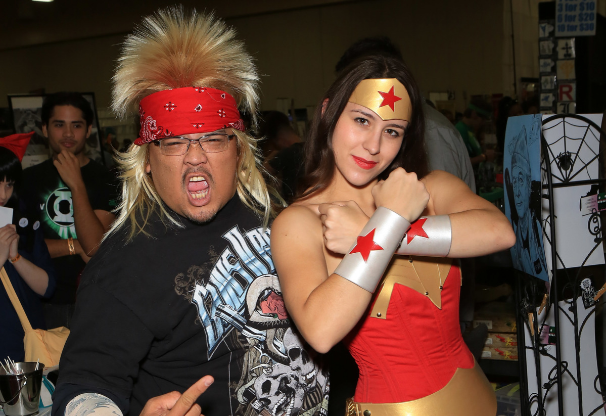 Free Isabelo, dressed as a 1980's rocker character and Sarah Paige, dressed as the character Wonder Woman from the