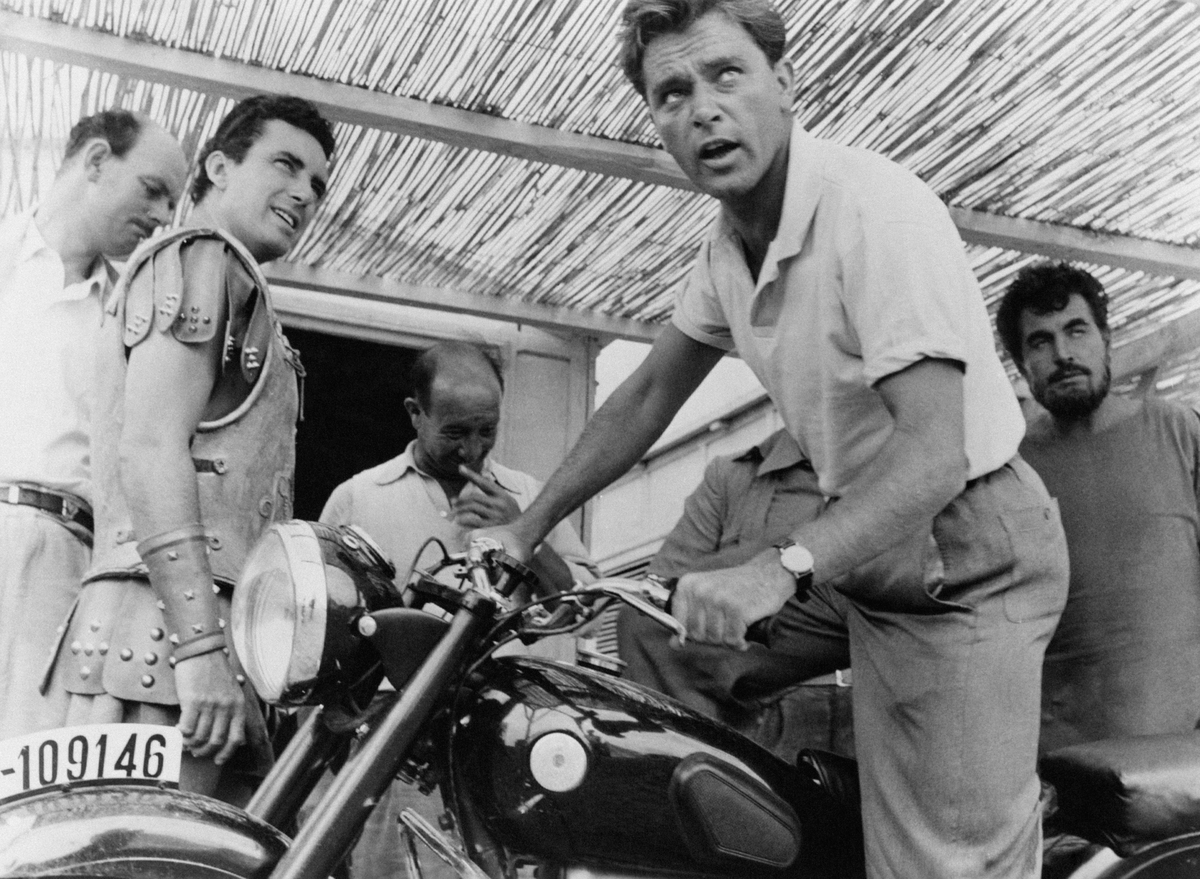British actor Richard Burton (Richard Jenkins) getting on a motorcycle on the set of the film Alexander the Great. 1956.