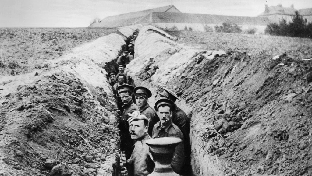 Soldiers lined up in a narrow trench during World War I