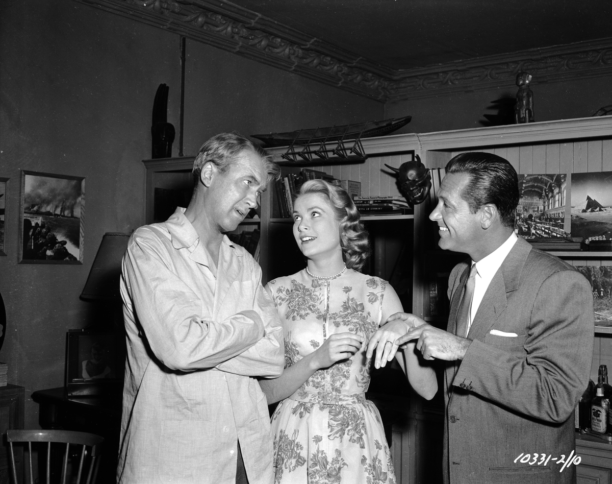 William Holden points out Grace Kelly's engagement ring to James Stewart in a moment of fun on the set of Hitchcock's 'Rear Window'.