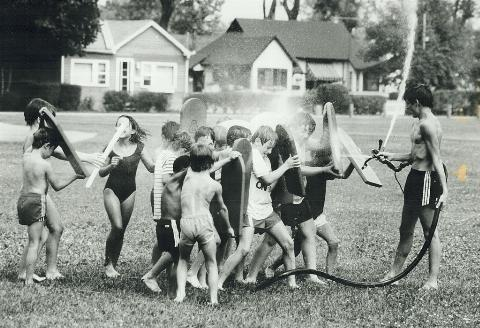 kids play with a water hose at summer camp