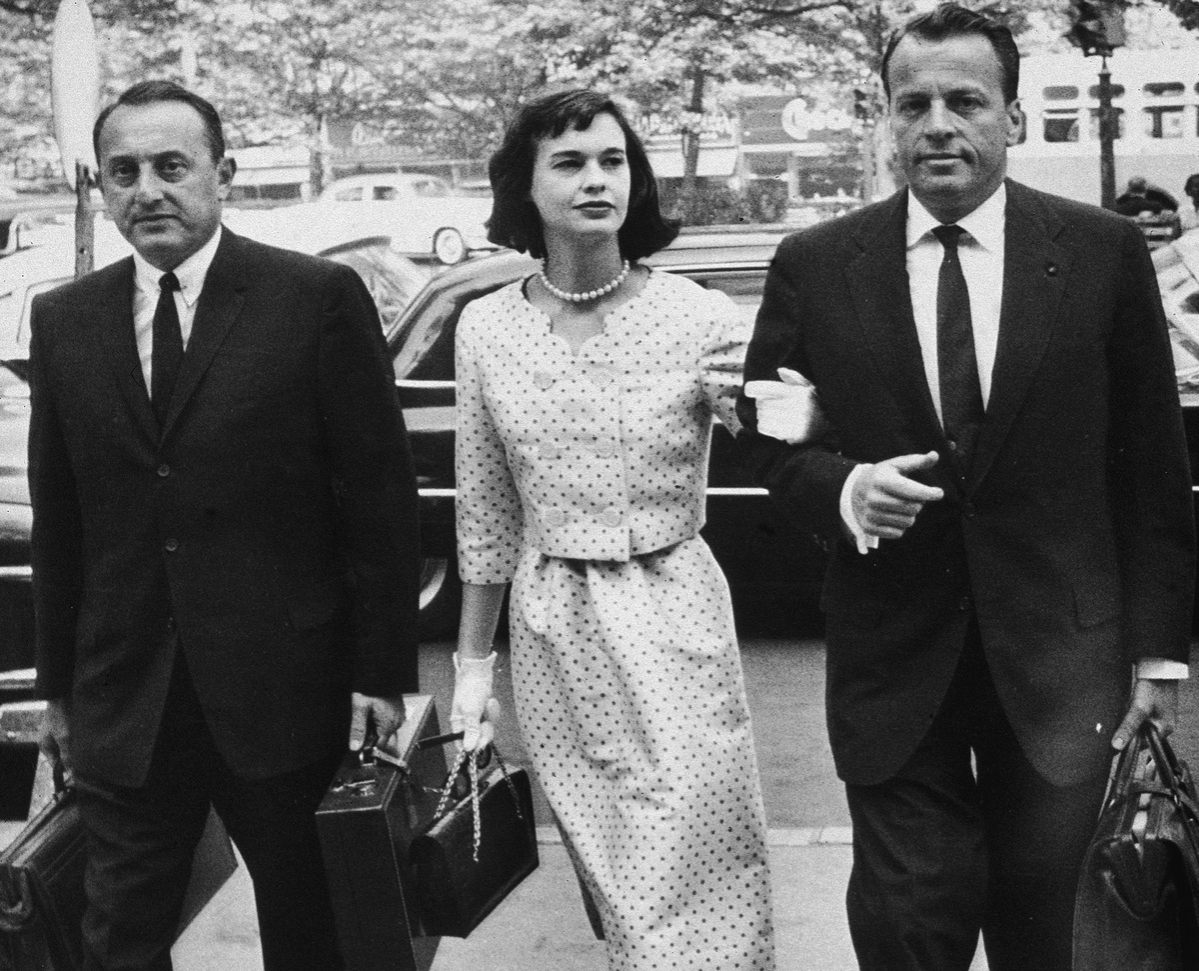 American heiress and socialite Gloria Vanderbilt walks with her attorneys on the way to a custody hearing with her former husband, Leopold Stokowski, June 5, 1959.