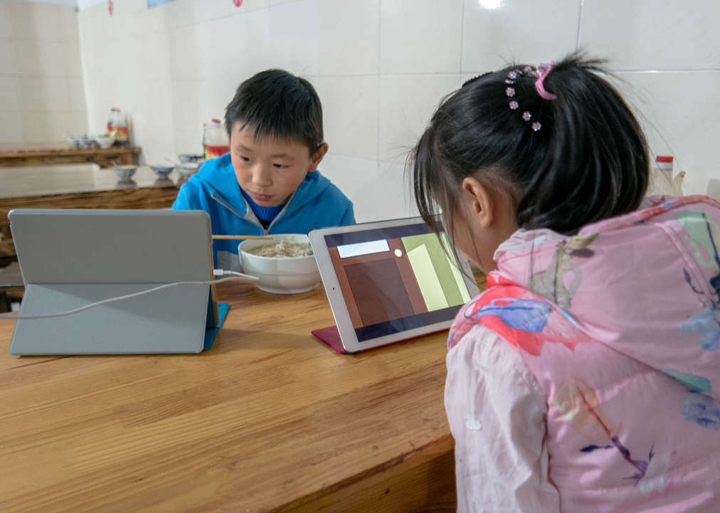 wo elementary school students watch cartoon video and play games on mobile device when having dinner.
