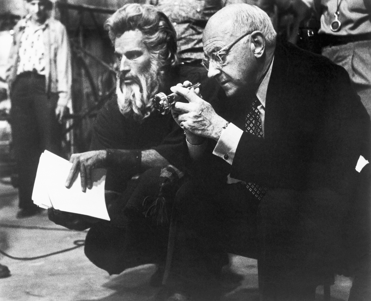 Picture shows actor, Charlton Heston(right), seated and talking to director, Cecil B. DeMill, on the set of the epic movie,