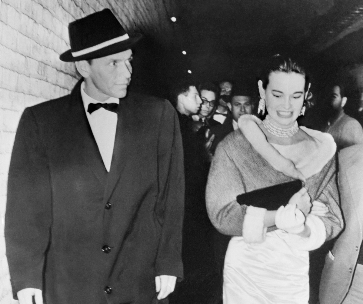 Heiress actress Gloria Vanderbilt goes backstage with her escort singer Frank Sinatra, to congratulate the players at the opening of the musical