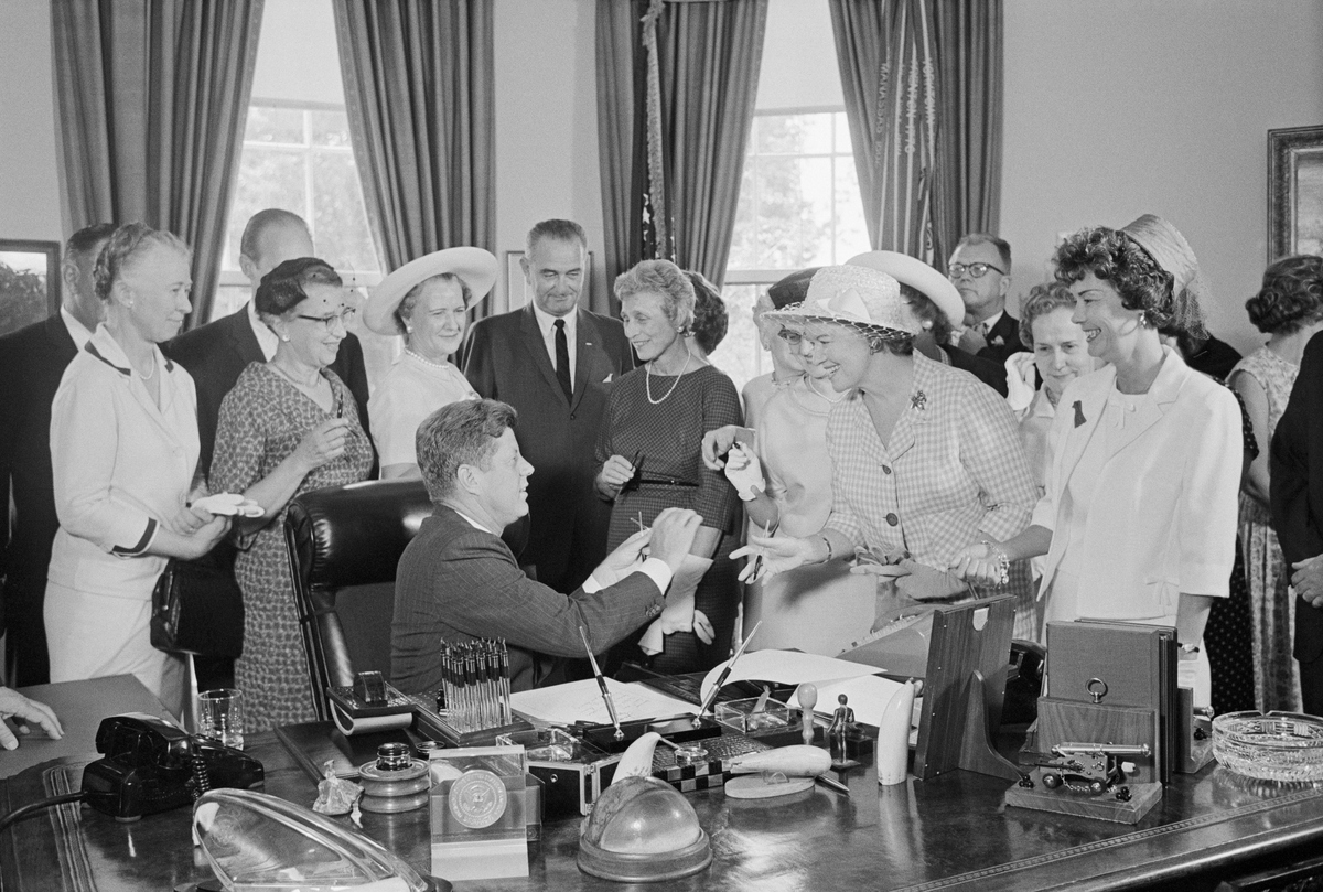 President Kennedy hands out pens during a ceremony at the White House today in which he signed into law a bill aimed at assuring women of paychecks equal to those of men doing the same work.