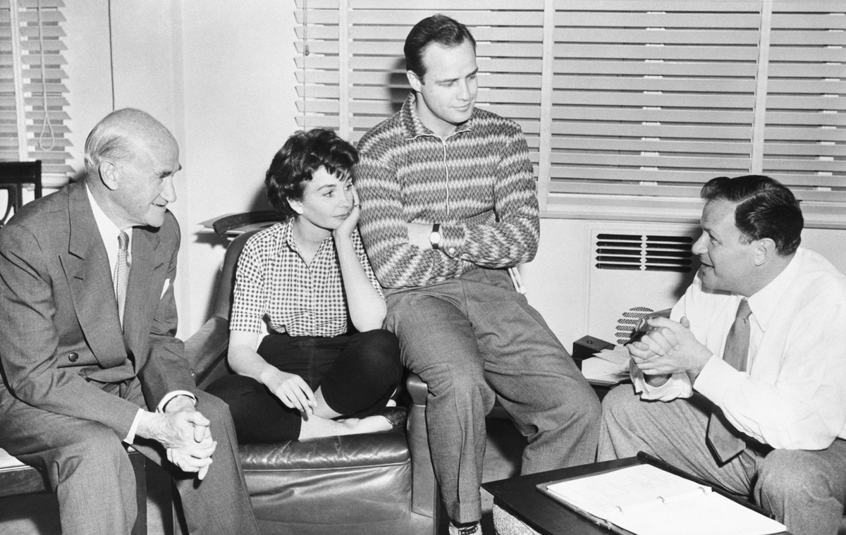 Samuel Goldwyn (L) imparts the news to Marlon Brando and Jean Simmons, who are co-starring in his forthcoming production of