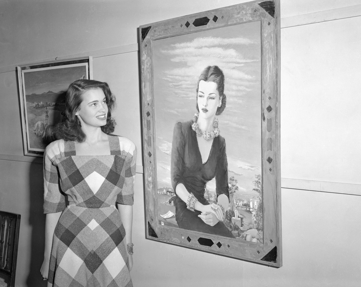 Gloria Vanderbilt stands beside her portrait painted by Miss Karin Van Leyden