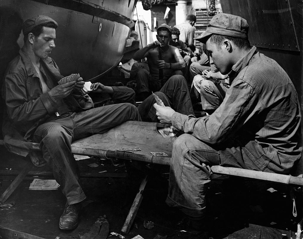 Marines play cards and clean their rifles on a ship bound for Iwo Jima