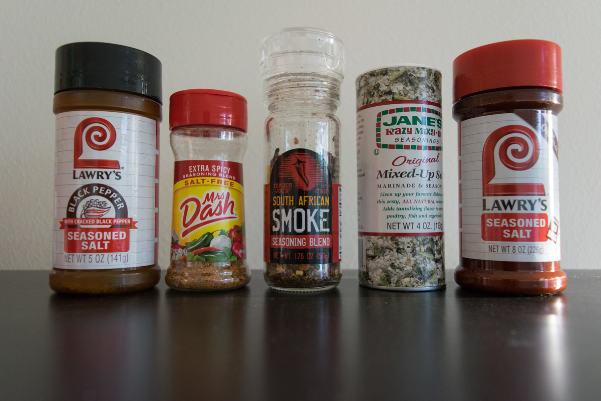 A variety of jars of seasonings in a row including Mrs Dash second from the left