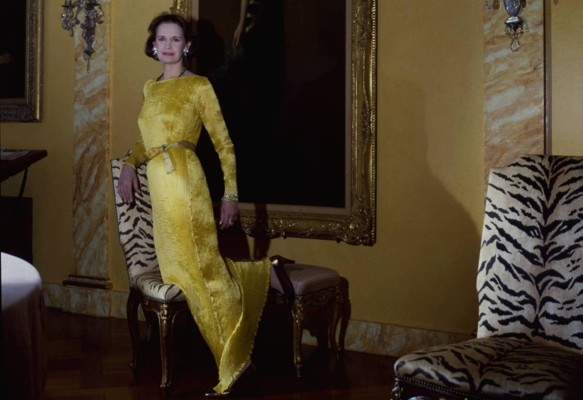 Fashion designer Gloria Vanderbilt wearing a pleated dress most likely by Fortuny and posing in front of a large portrait of her mother in her penthouse in Gracie Square in New York City.