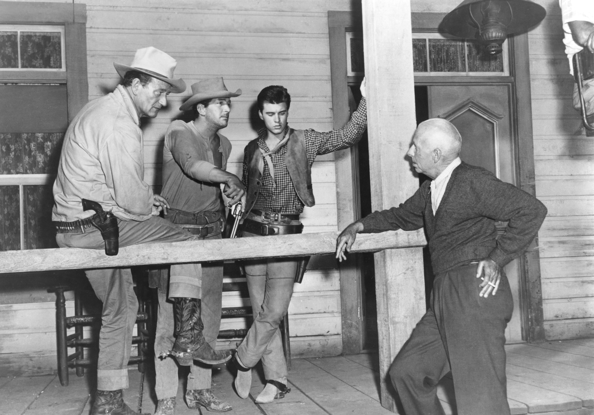American actors John Wayne, Dean Martin, and Ricky Nelson with director and producer Howard Hawks on the set of Hawks's movie Rio Bravo.