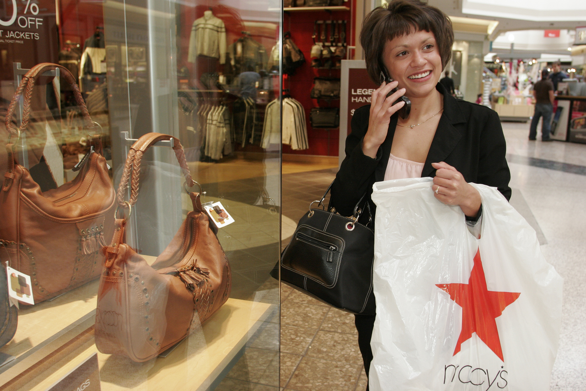 A woman talking on a cell phone holding a Macy's bag at Westfield Shoppingtown Southlake.