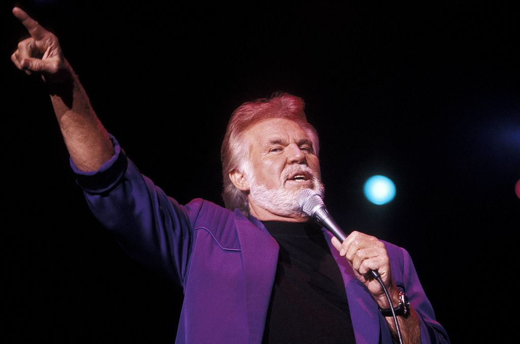 Rogers performing in a purple coat