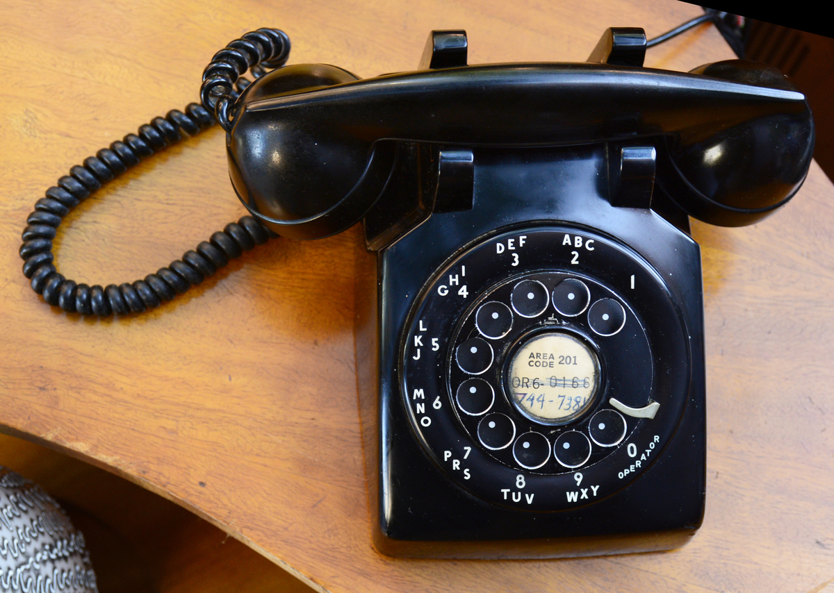 A vintage rotary dial telephone for sale at a flea market