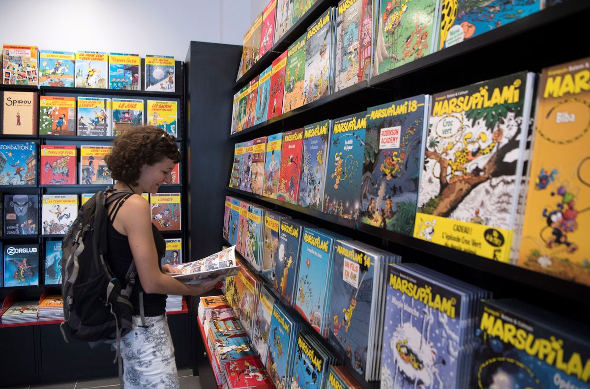 A woman reads a comics book in a shop during the official opening of the comics hero Spirou Provence Park in southern France