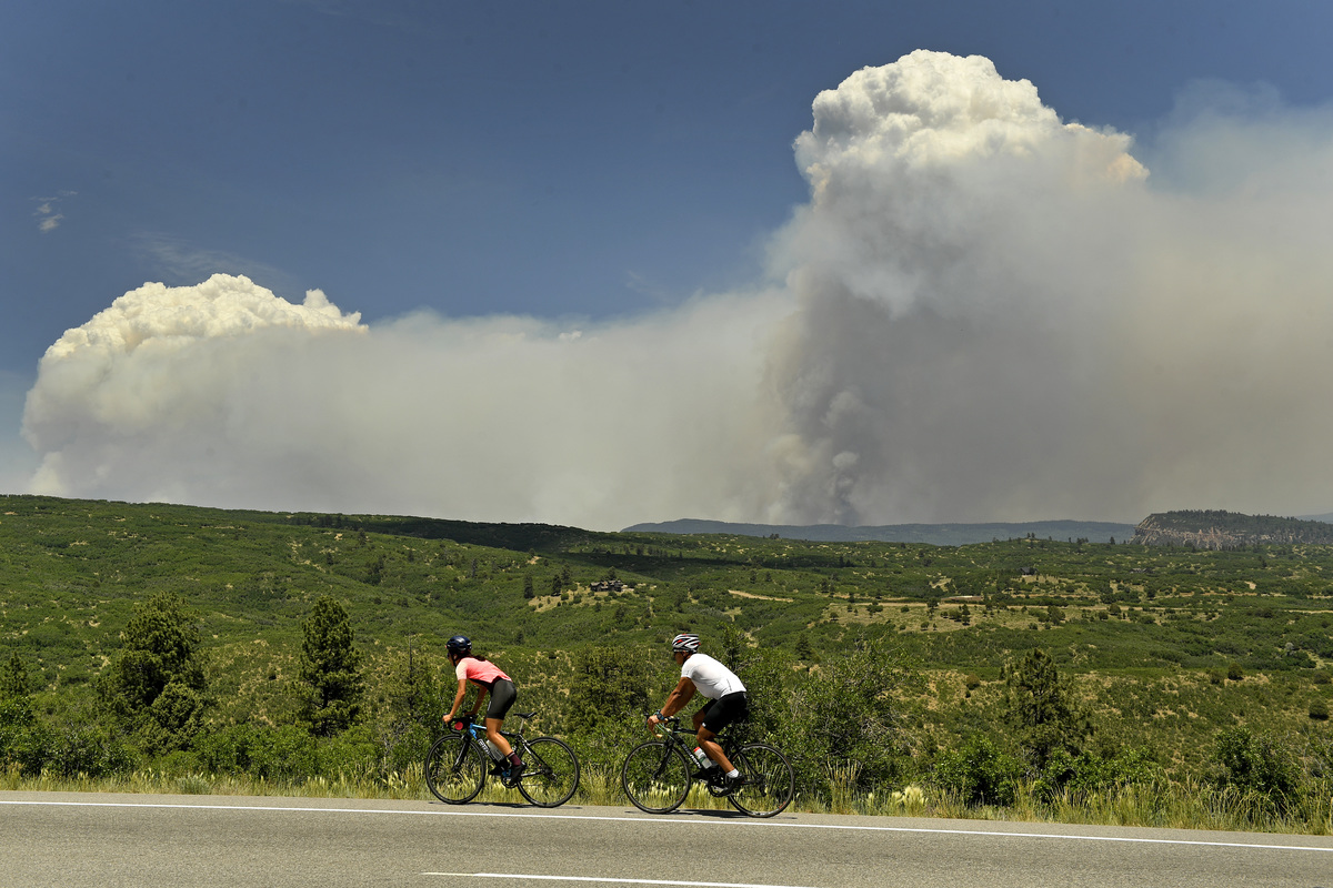 Cyclists look at the large plume of the 416 fire as they make their way up Highway 160 on June 12, 2018 near Hesperus, Colorado