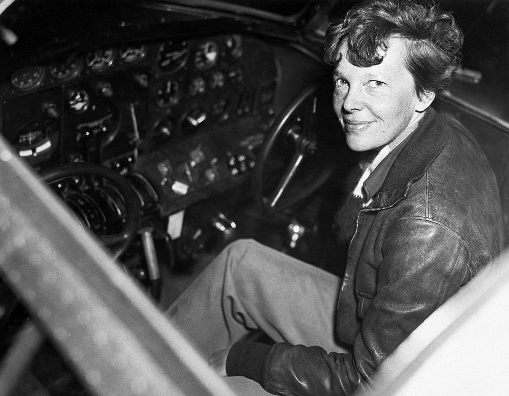 amelia earhart sitting in the cockpit of her plane