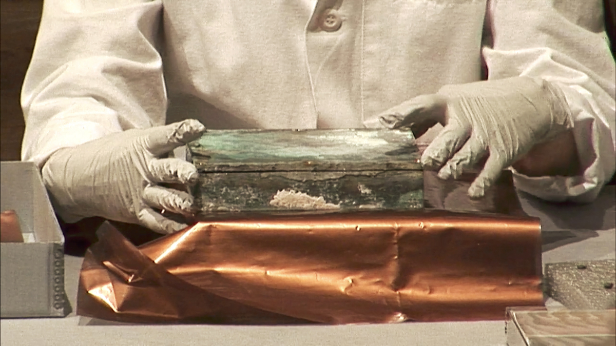 Time Capsule held with gloved hands