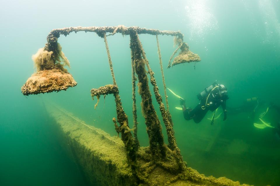 boat abandoned underwater with divers