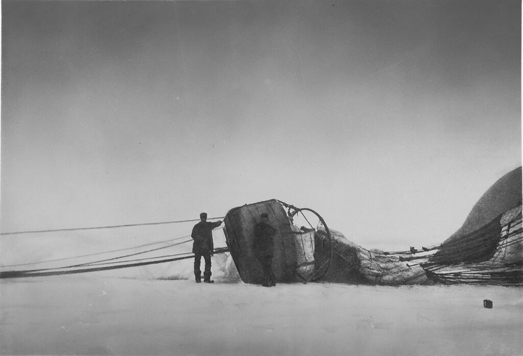 Two men standing next to the fallen balloon