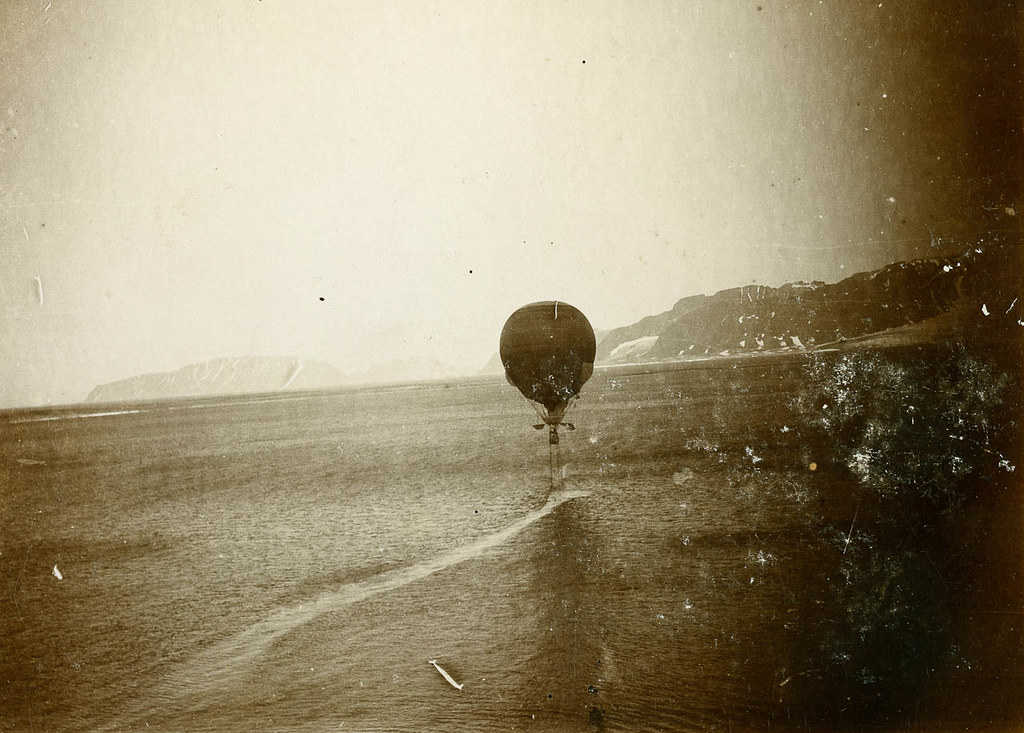 hot air balloon traveling further away from the camera, barely above the water