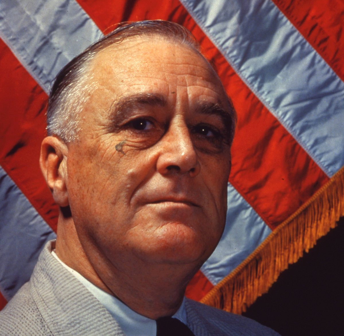 Portrait of American President Franklin Delano Roosevelt (1882 - 1945), 1940s. An American flag is in the background.