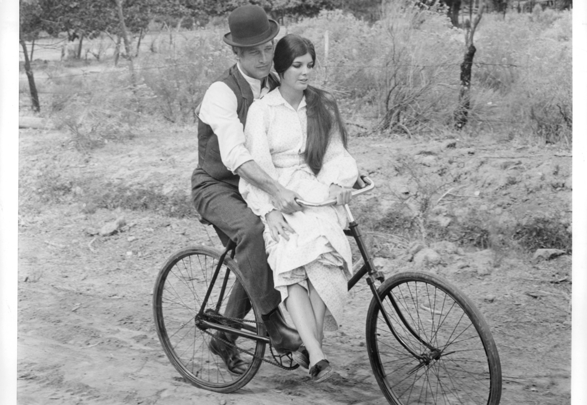 Paul Newman riding bike with Katharine Ross in a scene from the film 'Butch Cassidy And The Sundance Kid', 1969.