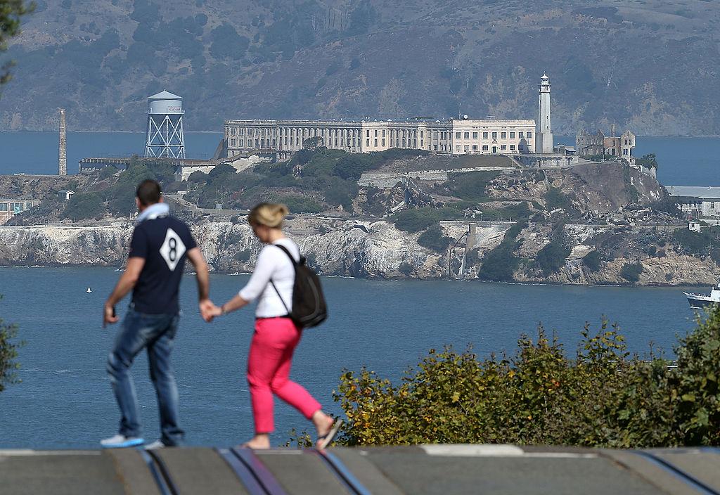 Pedestrians cross Hyde Street in front of Alcatraz Island