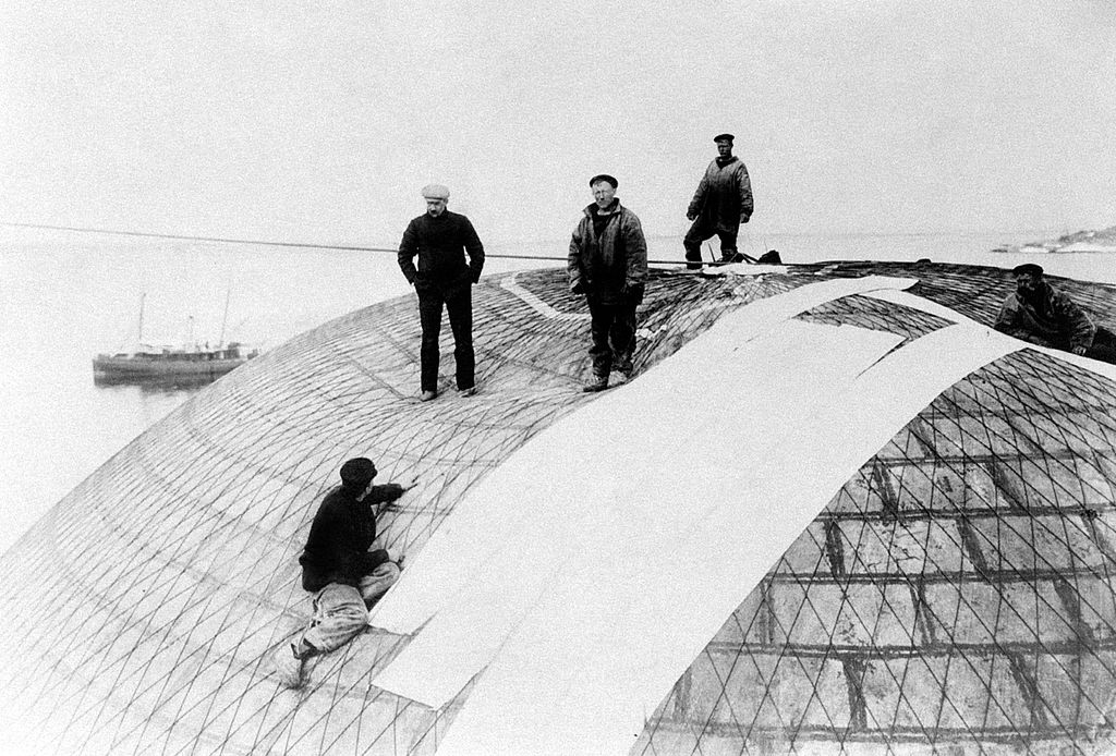 Men checking the waterproofing of the aerostatic balloon used by Swedish engineer and explorer Salomon August Andrée for his expedition-186174886