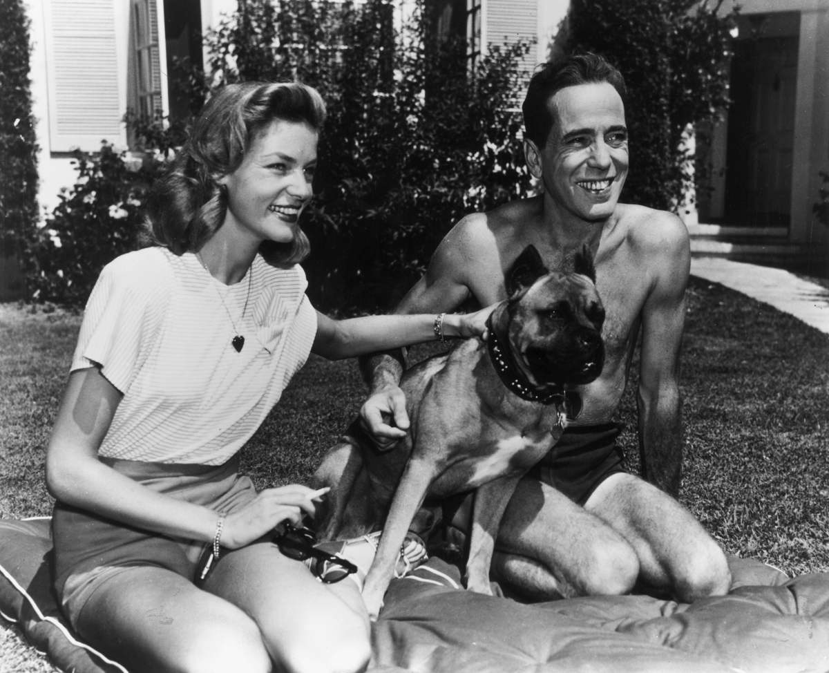 American actor Humphrey Bogart smiles as he kneels with his wife, actor Lauren Bacall, and their pet dog, on a cushion on their front lawn