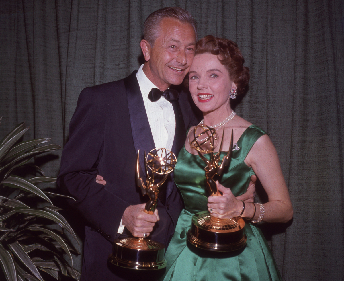 actors Robert Young and Jane Wyatt embrace while holding the Emmy Awards they won for their work on the television series, 'Father Knows Best'.